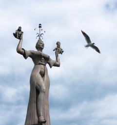 Statue der Imperia am Bodensee. Sie erinnert satirisch an das Konzil von Konstanz (1414–1418). Sie stellt eine üppige Kurtisane dar, der ein tiefes Dekolleté und ein Umhang, der nur von einem Gürtel notdürftig geschlossen wird, eindeutige erotische Ausstrahlung verleihen. Foto: Marita Blauth